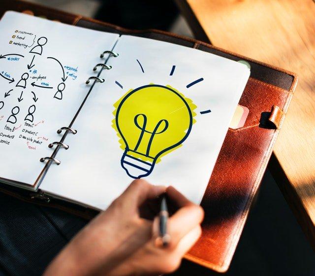 Človek, ktorý kreslí žiarovku do zápisníku
