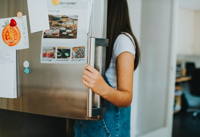 Žena pozerajúca sa do chladničky