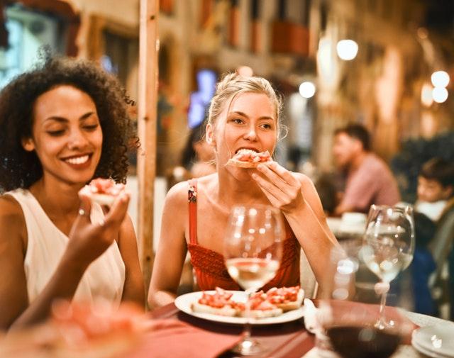 Ženy, ktoré jedia pizzu a na stole majú poháre s vínom.jpg