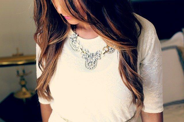 Žena v bielych šatách s výrazným náhrdelníkom na krku.jpg
