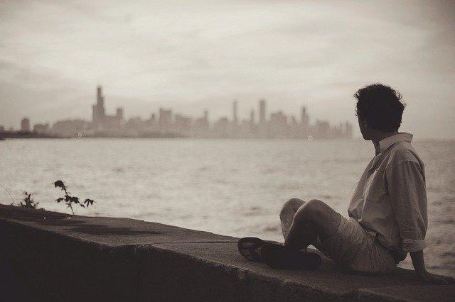 Muž sedí pri rieke